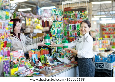 Happy mature woman chooses liquid fertilizer in bottle at market - stock photo
