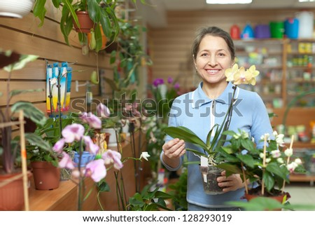 Happy mature woman chooses Phalaenopsis  in pot at flower shop