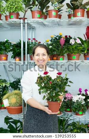 Happy mature woman chooses roses in pot at flower store - stock photo