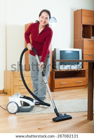 Happy mature woman cleaning with vacuum cleaner - stock photo