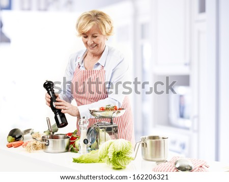Happy mature woman cooking in her kitchen - stock photo