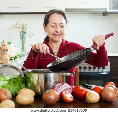 Happy mature woman cooking lent diet lunch  with skillet in  kitchen - stock photo
