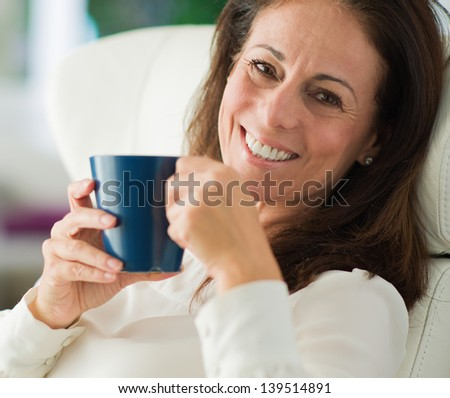 Happy Mature Woman Drinking Coffee, Indoors - stock photo
