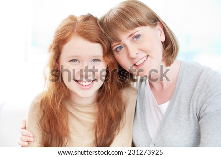 Happy mature woman embracing her pretty teenage daughter - stock photo