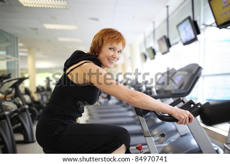 Happy mature woman exercising on a stationary bike in gym. - stock photo