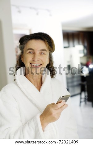 happy mature woman in a bathroom checks her phone