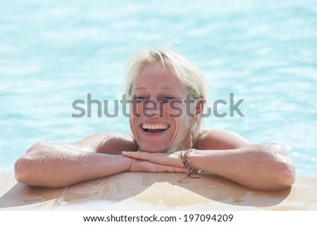 Happy mature woman in swimming pool - stock photo