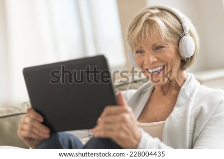 Happy mature woman looking at digital tablet while using headphones at home - stock photo