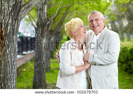 Happy mature woman looking at her husband while having rest outside - stock photo