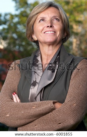 Happy mature woman looking at the sky. - stock photo
