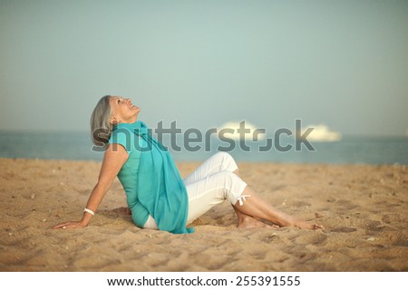 Happy mature woman on beach - stock photo