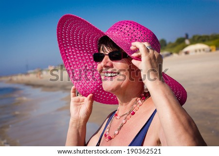 Happy mature woman on the beach. Selective focus. - stock photo