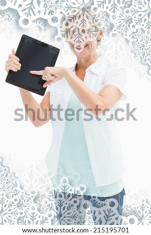 Happy mature woman pointing to tablet pc against snowflakes on silver - stock photo