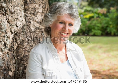 Happy mature woman sitting on tree trunk looking at camera in park - stock photo
