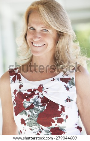 Happy mature woman smiling outdoors - stock photo