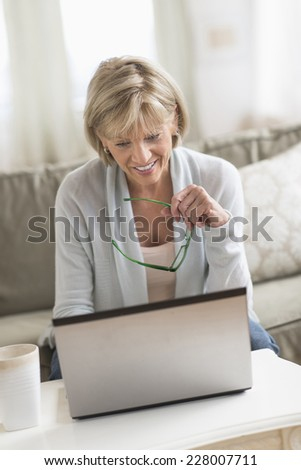 Happy mature woman using laptop while holding glasses in living room - stock photo