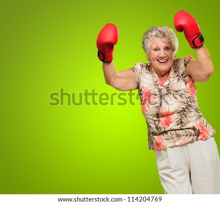 Happy Mature Woman Wearing Boxing Glove Cheering Isolated On Green Background - stock photo