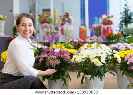 Happy mature woman with chrysanthemum at flower store