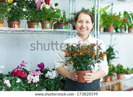 Happy mature woman with citrus plant surrounded by different flowers in flower store - stock photo
