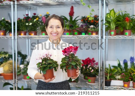 Happy mature woman with Cyclamen plant surrounded by different flowers - stock photo