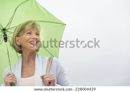 Happy mature woman with green umbrella looking away against clear sky - stock photo