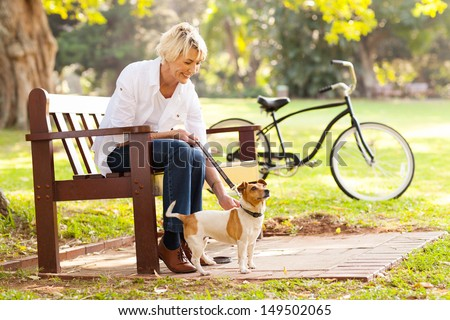 happy mature woman with pet dog outdoors - stock photo