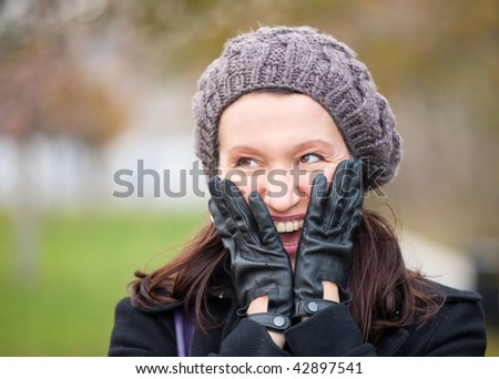 happy mature woman with winter clothes and head in hands