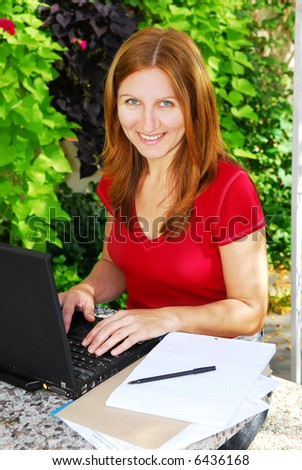 Happy mature woman working on a portable computer in her garden - stock photo