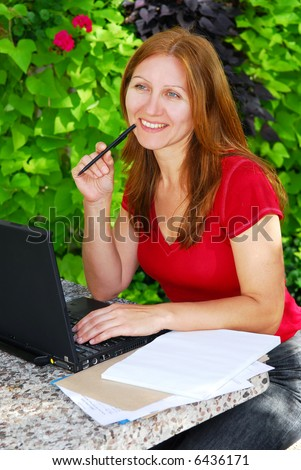 Happy mature woman working on a portable computer in her garden