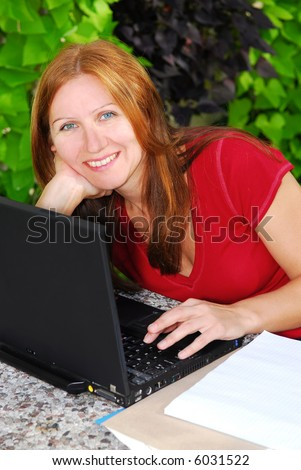 Happy mature woman working on portable computer at home, small business owner - stock photo