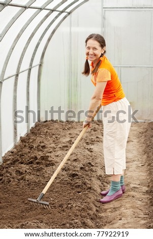Happy mature  woman  working with rake in greenhouse