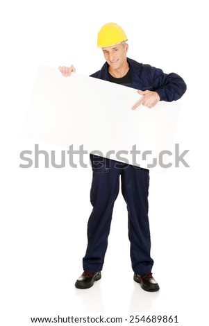 Happy mature worker presenting empty banner.