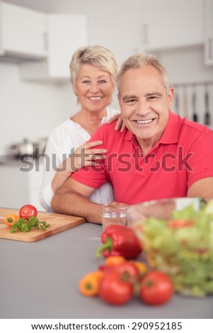 Happy Matured Couple at the Kitchen Smiling at Camera While Preparing Healthy Recipe for Dinner.