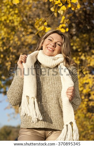 Happy matured woman in front of yellow autumn leaves outdoor