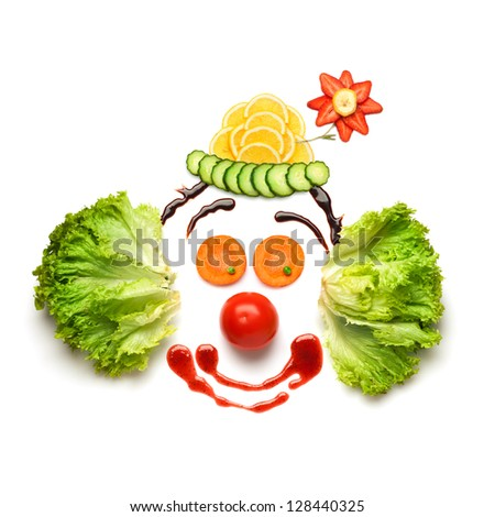 Happy meal for opponents of fast-food. A nice and funny edible clown, made of strawberries, lemons, salad and so on. - stock photo