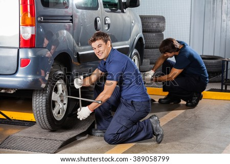 Happy Mechanic Fixing Car Tire At Repair Shop - stock photo