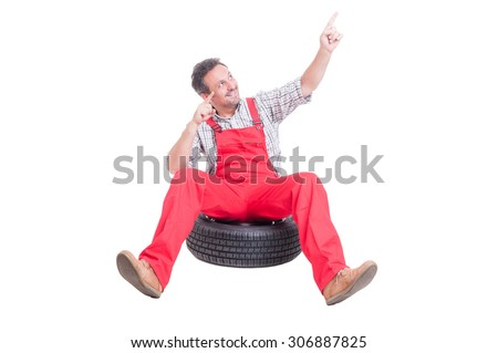 Happy mechanic sitting on car wheel and dancing with hands up - stock photo