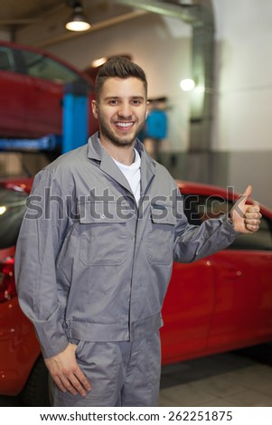 Happy mechanic. Smiling man in workwear showing thumb up.