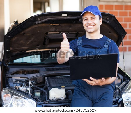 Happy mechanic using a laptop computer to check a car engine - stock photo