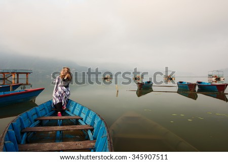 Happy meditate girl with blanket sitting in old boat on mountain lake early morning. Clouds and fog over the lake, loneliness, tranquility, relaxation - stock photo