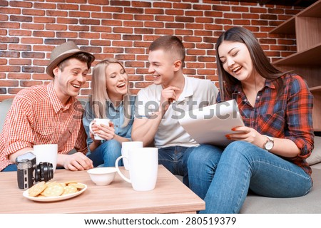 Happy meeting. Young smiling girl writing in a notebook while her friend laughing discussing something funny drinking tea, camera cookies and cups on the table  - stock photo
