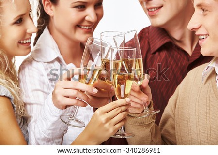 Happy men and women clinking with champagne - stock photo