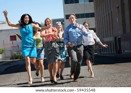 Happy men and women running down the street. - stock photo