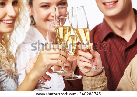 Happy men and women toasting with bubbly champagne - stock photo