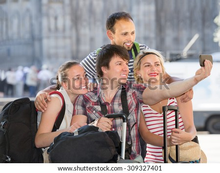 Happy men and women with luggage doing selfie at vacation