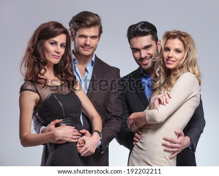 happy men embracing their women and looking at the camera - stock photo