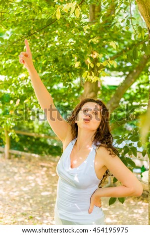 Happy menopausal woman with long brown wavy hair kisses while pointing the finger of right hand upward
