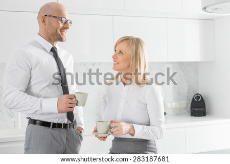 Happy mid adult business couple having coffee in kitchen - stock photo