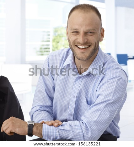 Happy mid-adult businessman sitting at office, laughing. - stock photo