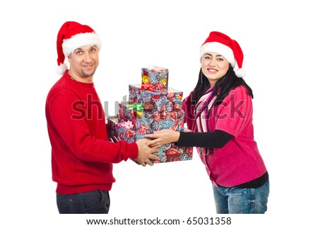 Happy mid adult couple holding Christmas presents and looking at camera isolated on white background